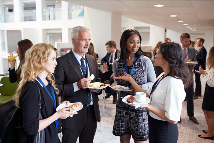 four people holding food and networking