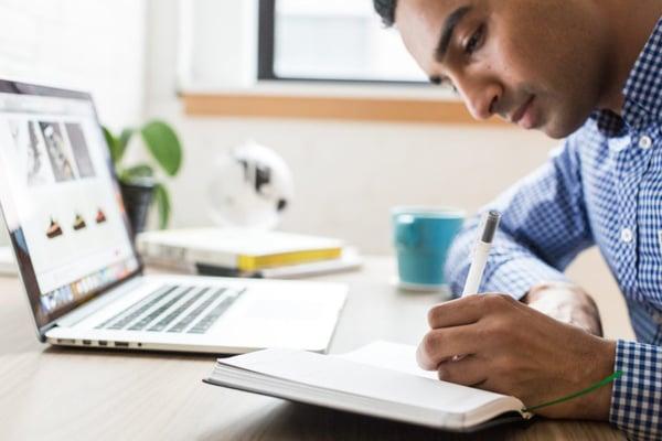 businessman using ballpoint men next to laptop