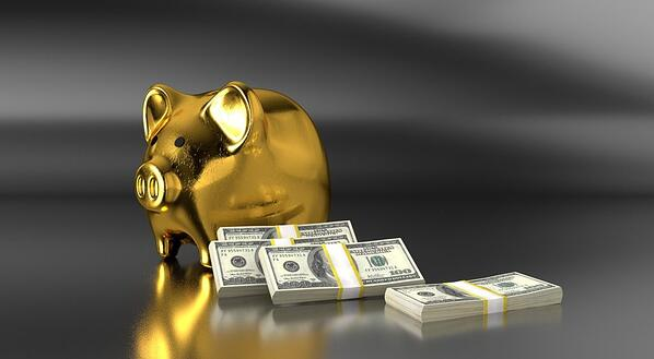 golden piggy bank with bills