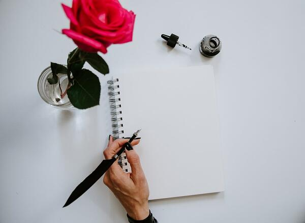 person holding black pen writing on white notebook
