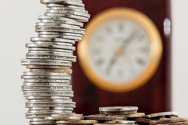 silver and gold coins in front of a clock.