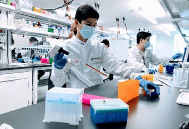 person in laboratory using a pipette